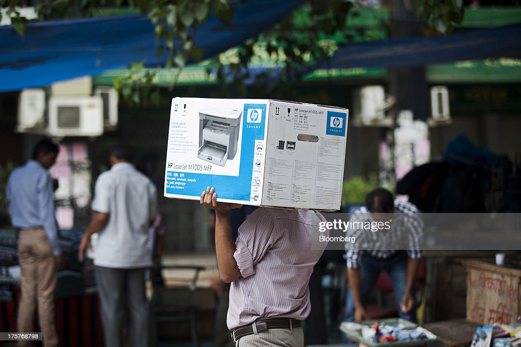 A man carries a boxed Hewlett-Packard Co. LaserJet printer in Nehru Place IT Market, a hub for the sale of electronic goods and computer accessories, in downtown New Delhi, India, on Wednesday, Aug. 7, 2013. India's consumer price index (CPI) figures for July are scheduled to be released on August 12. Photographer: Graham Crouch/Bloomberg via Getty Images