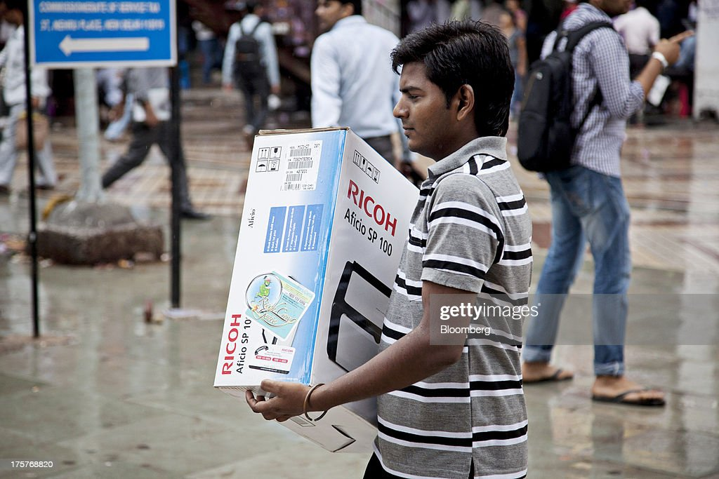 A man carries a boxed Ricoh Co. Aficio SP 100 printer in Nehru Place IT Market, a hub for the sale of electronic goods and computer accessories, in downtown New Delhi, India, on Wednesday, Aug. 7, 2013. India's consumer price index (CPI) figures for July are scheduled to be released on August 12. Photographer: Graham Crouch/Bloomberg via Getty Images