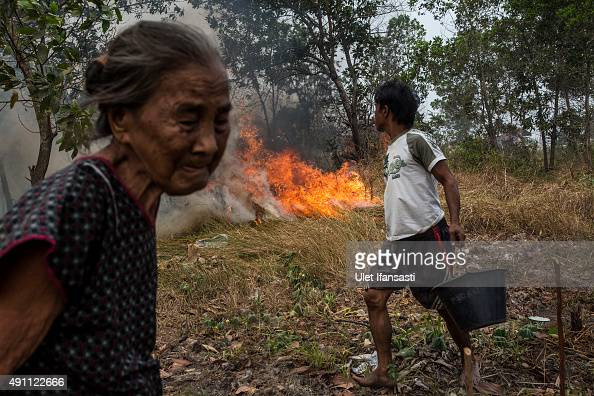 A man carries a bucket of water as they try to extinguish the fire on burned peatland and fields near his house at Ogan Ilir district on October 3...