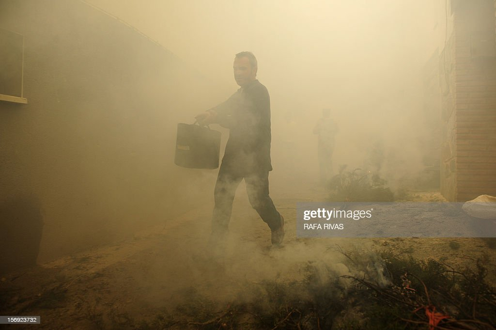 A man carries a bucket of water through the smoke during the celebration of the 'Procession of smoke' with San Andres, Saint Patron of Arnedillo on November 25, 2012, in the northern Spanish village of Arnedillo.