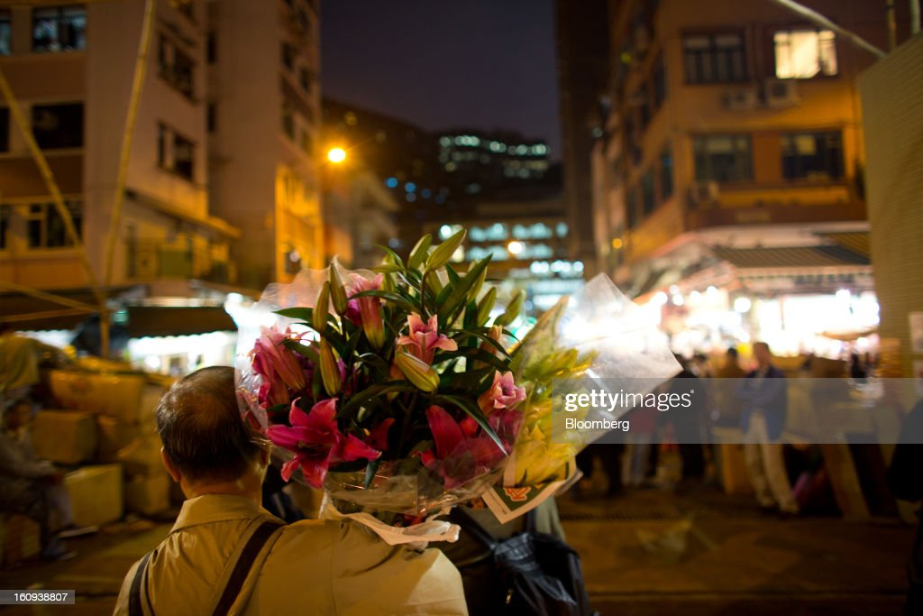 A man carries a bunch of flowers in the Mongkok district of Hong Kong, China, on Thursday, Feb. 7, 2013. Hong Kong's stock market will be shut for three days next week for the Lunar New Year holidays, while markets in mainland China will be closed for the whole week. Photographer: Lam Yik Fei/Bloomberg via Getty Images