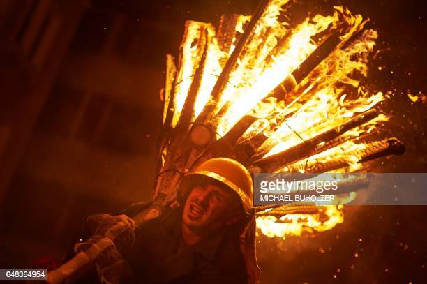 A man carries a burning bundle of pinewood chips on his shoulders during the 'Chienbase' procession on March 5 2017 in Liestal northern Switzerland...