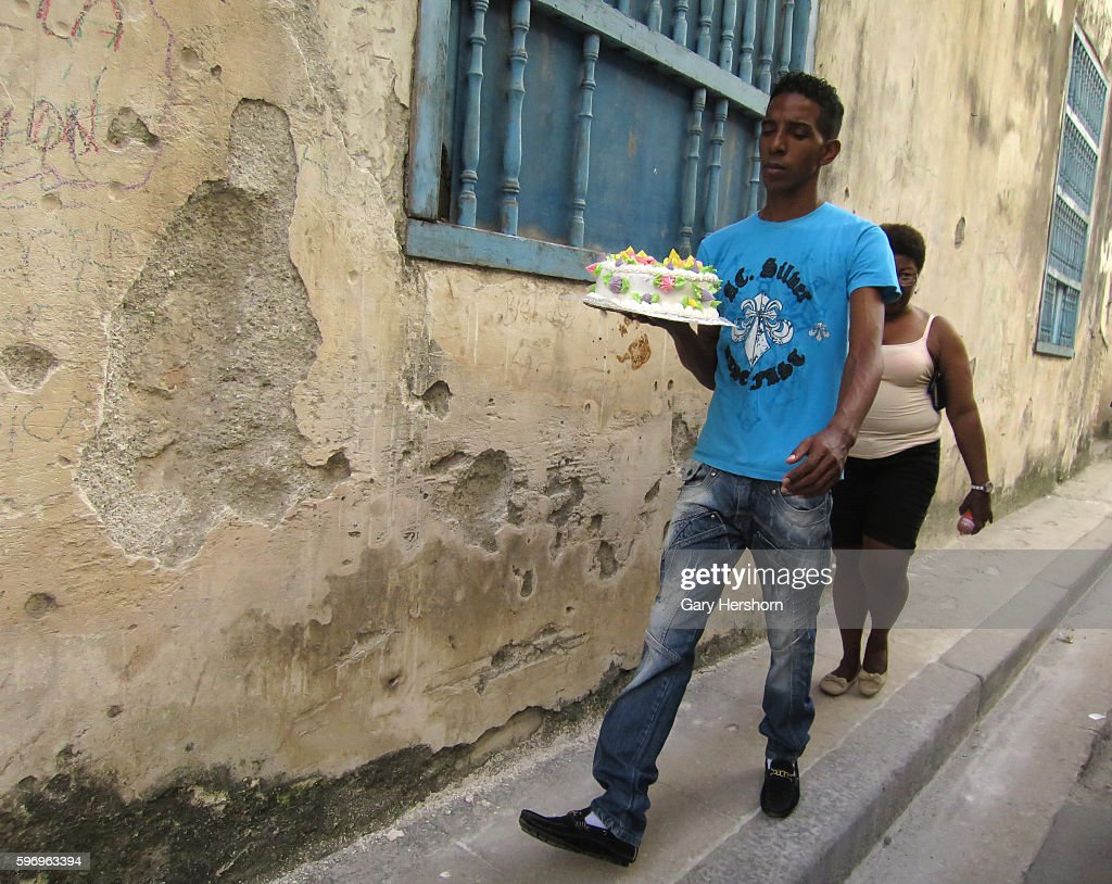 A man carries a cake down the street in the old city in Havana Cuba October 10 2014