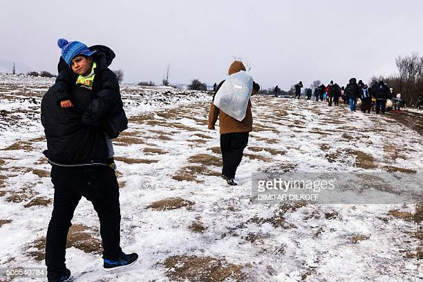 A man carries a child as migrants and refugees walk along snow covered tracks after crossing the Macedonian border into Serbia near the village of...