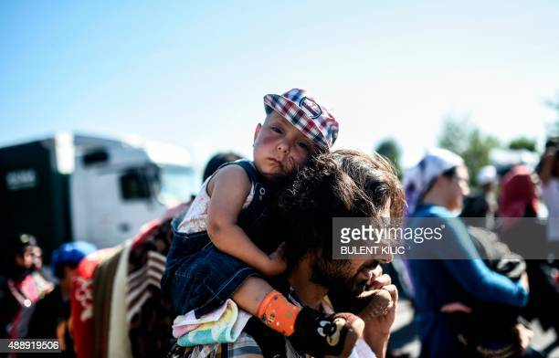 A man carries a child as Syrian migrants and refugees march along the highway towards the TurkishGreek border at Edirne on September 18 2015 Several...