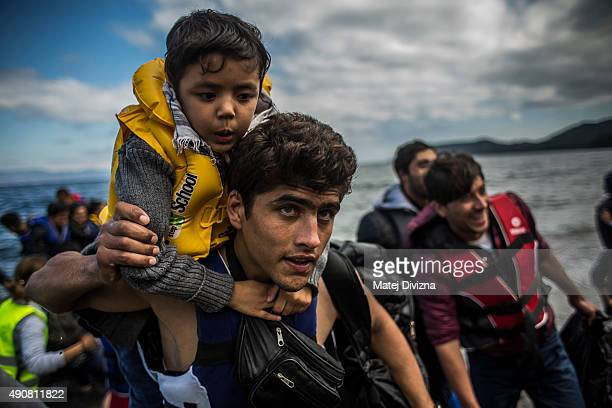 A man carries a child as they arrives with other refugees on the shores of the Greek island of Lesbos after crossing the Aegean sea from Turkey on a...