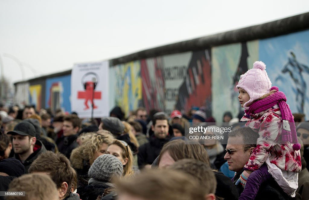A man carries a child on his shoulders in a crowd awaiting David Hasselhoff (not in pic) who tours the East Side Gallery on March 17, 2013 to protest the demolition of parts of the wall for a real estate project. The former Bay watch star was in the German capital to lend his support to the movement that wants to preserve the 1,3km long stretch of the cold war symbol and keep the land along river Spree as public land.