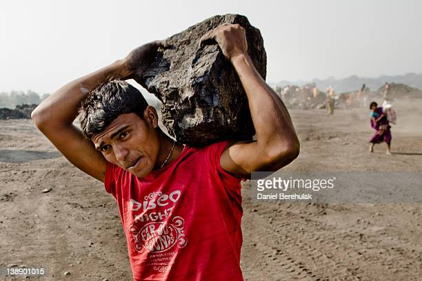 A man carries a chunk of coal as villagers work to scavenge coal illegally from an opencast coal mine in the village of Jina Gora on February 11 2012...