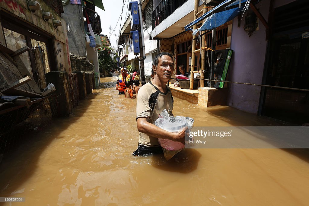 A man carries a cooking pot from his home in a flooded neighborhood after floodwaters receded enough for him to get to his house on January 19, 2013 in Jakarta, Indonesia. Floodwaters receded today after three days of heavy flooding which left thousands of people's homes underwater. According to Indonesian police the death toll has reached 15.