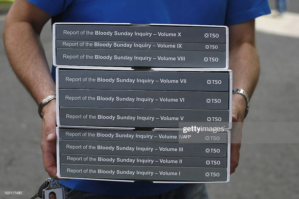 A man carries a copy of the long-awaited Saville Inquiry report into Bloody Sunday, outside the Guildhall in Londonderry on June 15, 2010. Publication of the report was greeted with cheers in Londonderry, Northern Ireland's second city, where relatives of those who died joined thousands waiting to see the contents of the 5,000-page report. The killings, when British soldiers opened fire on a civil rights march in Londonderry, was one of the most controversial in Northern Ireland's history, and there had been fears the report could re-open wounds. AFP PHOTO / POOL / Paul Faith