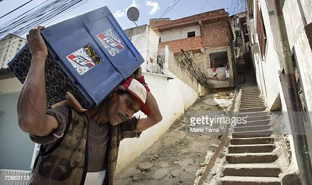 A man carries a crate of beer in a poor barrio November 28 2006 in Caracas Venezuela President Hugo Chavez is widely popular in the poor barrios of...