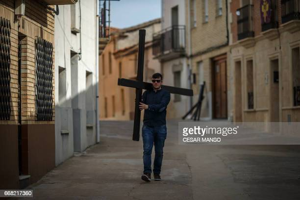 A man carries a cross before the Ecce Homo Passion procession during Holy Week in the northwestern Spanish village of Fuentesauco on April 13 2017...