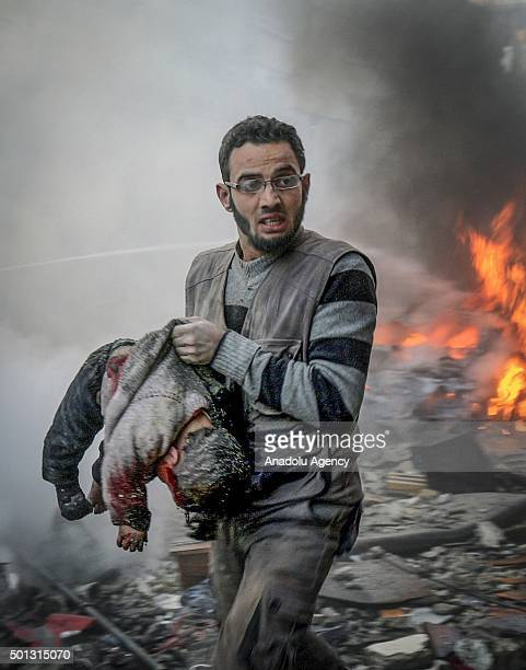 A man carries a dead Syrian child after the airstrikes conducted by Syrian army at marketplace in Hamuriye neighborhood of Damascus Syria on December...