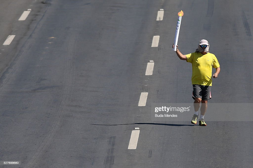 A man carries a fake torch during the the Olympic Flame torch relay on May 3, 2016 in Brasilia, Brazil. The Olympic torch will pass through 329 cities from all states from the north to the south of Brazil, until arriving in Rio de Janeiro on August 5, to lit the cauldron.