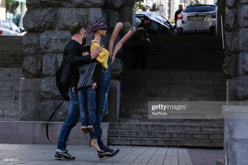 A man carries a female and a boy mannequins at Khreshchatyk street in Kyiv, Ukraine, October 10, 2017.