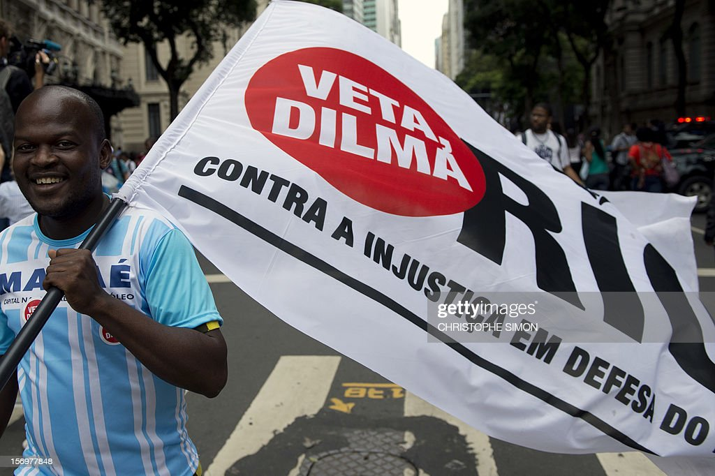 A man carries a flag during a demonstration demanding Brazilian President Dilma Roussef to veto a bill that would redistribute oil royalties in favor of non-oil producing states, in Rio de Janeiro, Brazil, on November 26, 2012. Both Rio de Janeiro's mayor Eduardo Paes and governor Sergio Cabral warned that the new oil royalties share-out plan will jeopardize the financing of the 2014 World Cup and the 2016 summer Olympics. AFP PHOTO/Christophe Simon