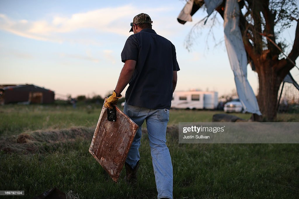 A man carries a framed photograph as he looks through debris to find personal items after a series of tornadoes that ripped through the area a day earlier on June 1, 2013 in El Reno, Oklahoma. A series of tornadoes ripped through the area on Friday evening killing at least nine people, injuring many others and destroying homes and buildings.