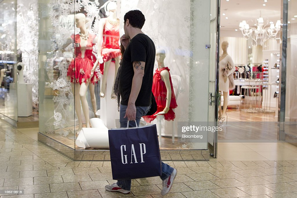 A man carries a Gap Inc. shopping bag while walking through the Fair Oaks Mall in Fairfax, Virginia, U.S., on Monday, Nov. 12. 2012. Sales at U.S. retailers probably fell in October for the first time in four months economists said before a report on Nov. 14. Photographer: Andrew Harrer/Bloomberg via Getty Images