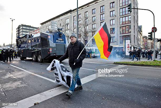 A man carries a German flag as supporters of Pegida Hogesa and other rightwing populist groups protest against the New Year's Eve sex attacks on...