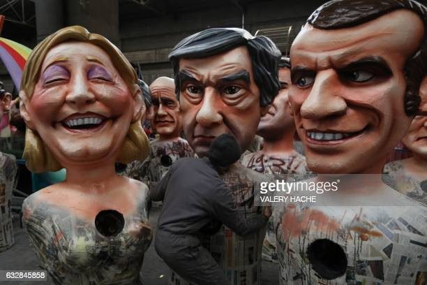 A man carries a giant figure depicting rightwing presidential candidates Francois Fillon next to others depicting far right presidential candidate...