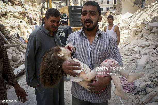 A man carries a girl after warcraft belonging to the Syrian army carried out airstrikes on residential areas in the opposition controlled Tariq alBab...