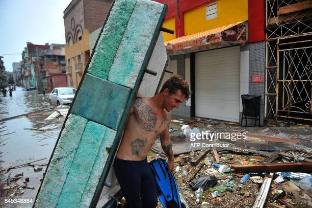 A man carries a homemade boat along a street of Havana on September 10 2017 Deadly Hurricane Irma battered central Cuba on Saturday knocking down...