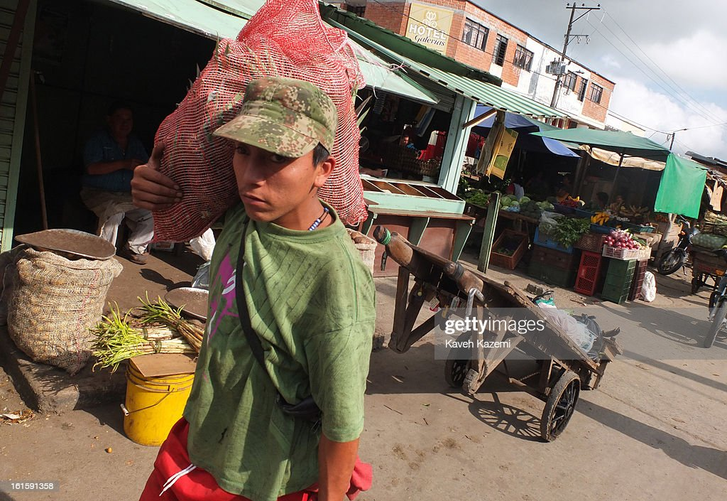 A man carries a large bag of Papaya (potatoes) on his shoulder in Barrio Bolivar day market on January 23, 2013 in Popayan, Colombia.