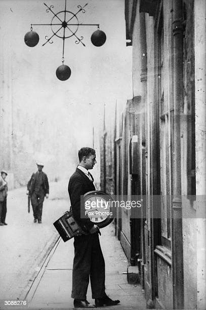 A man carries a large clock into a pawnbroker's passing under the three balls which are the international symbol of this profession