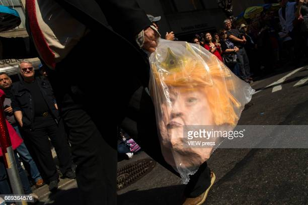 A man carries a mask of US president Trump as he attends the Annual Easter parade on April 16 2017 in New York City The Easter Parade and Easter...