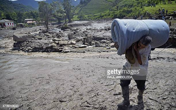 A man carries a mattress after a landslide in Salgar municipality Antioquia department Colombia on May 18 2015 A massive landslide tore through a...
