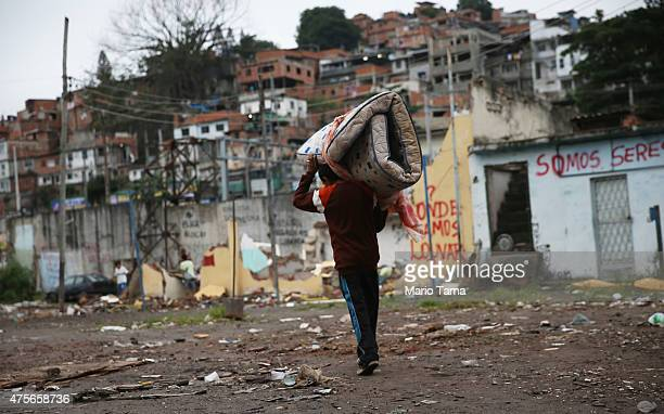 A man carries a mattress in an area where homes once stood in the MetroMangueira community or 'favela' located approximately 750 meters from Maracana...
