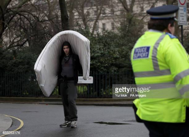 A man carries a mattress outside the pound15 million Grade II listed mansion on Belgrave Place London which has been squatted by the Autonomous...