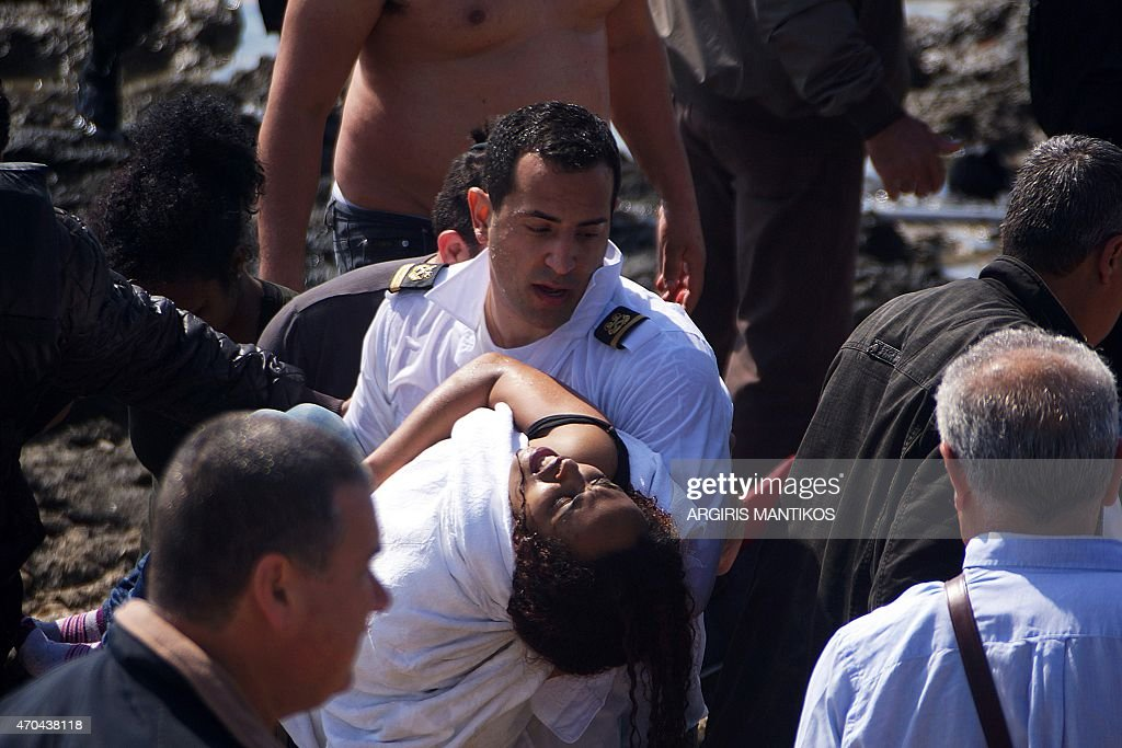 A man carries a migrant woman as local residents and rescue workers help migrants after their boat sank off the island of Rhodes southeastern Greece...