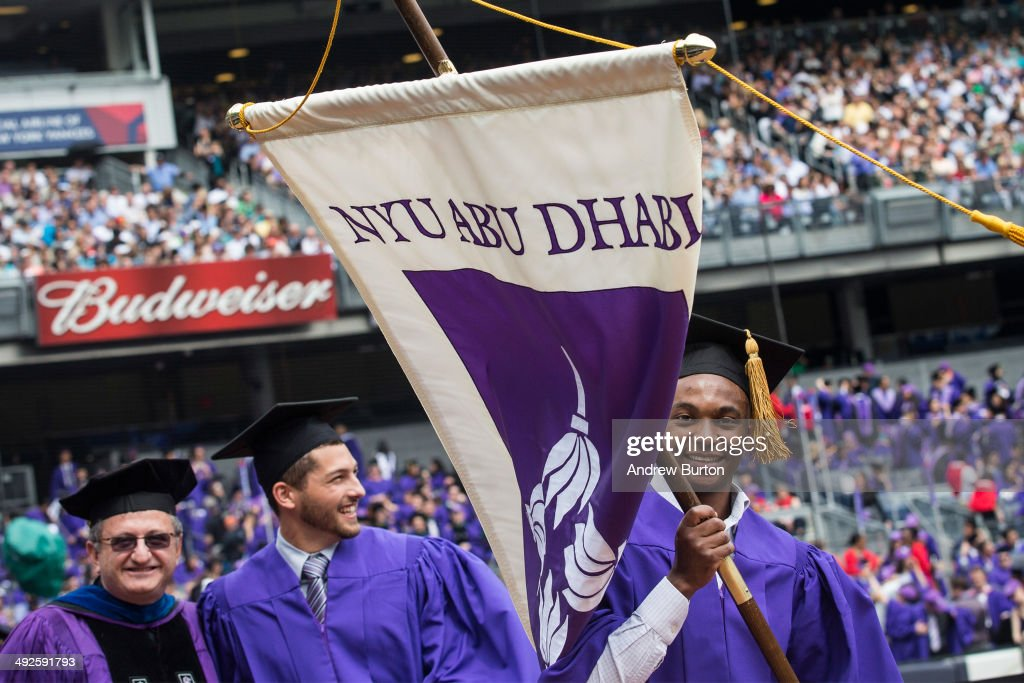 A man carries a New York University (NYU) Abu Dhabi flag during the commencement ceremonies for New York University at Yankee Stadium on May 21, 2014 in the Bronx borough of New York City. NYU has recently been embroiled in a scandal over poor living conditions of workers building a new campus for NYU in Abu Dhabi, U.A.E. Janet Yellen, Chair of the Board of Governors of the Federal Reserve System, received an honorary doctorate and was the 2014 commencement speaker.