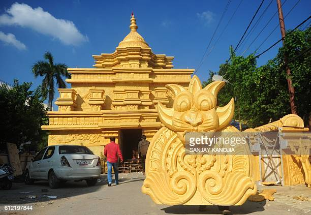 A man carries a painted polystyrene crafted design to dry it in the sunlight as they make a replica of Tirupati Balaji temple outside an incomplete...