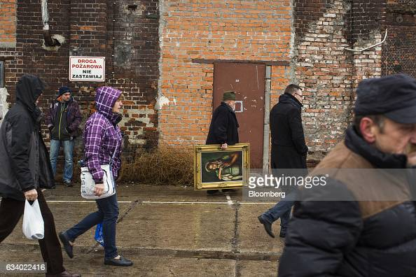 A man carries a painting purchased from a flea market in Wroclaw Poland on Sunday Feb 5 2017 Polands economy expanded at the weakest pace in three...