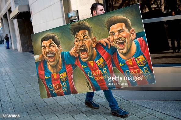 TOPSHOT A man carries a painting representing Spanish Barcelona's Uruguayan forward Luis Suarez Barcelona's Brazilian forward Neymar and Barcelona's...