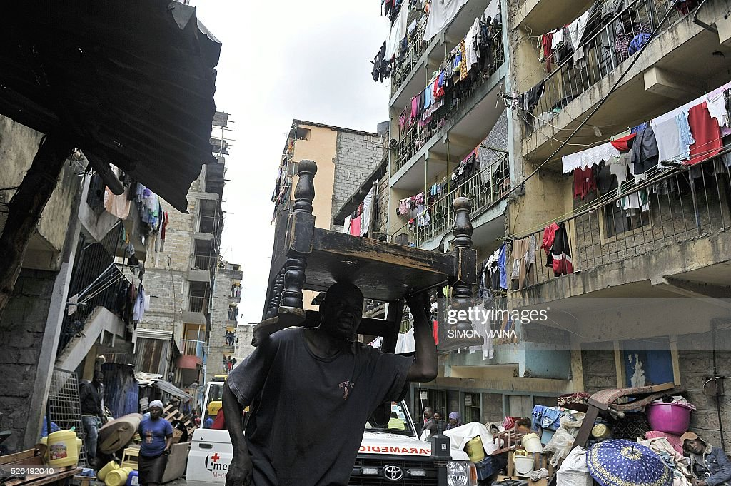 A man carries a piece of furniture as people leave the vicinity of a collapsed building in Nairobi on April 30, 2016. Rescuers in the Kenyan capital made desperate efforts Saturday to free survivors including a woman and child trapped in a building that collapsed in storms that have left a total of 17 people dead. / AFP / SIMON