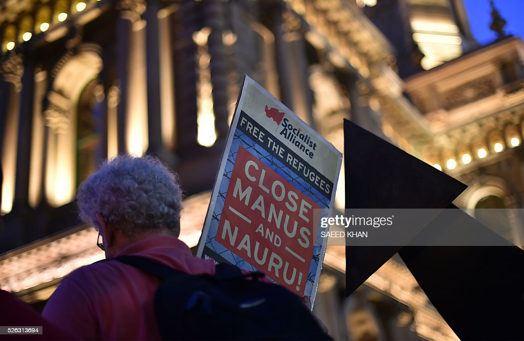 A man carries a placard during a candle light-vigil for an Iranian refugee, who died after setting himself on fire, in Sydney on April 30, 2016. The 23-year-old known as Omid set fire to himself on April 27, 2016 on the remote Pacific island where he had been sent by Australia, which refuses to resettle boat people even if found to be genuine refugees. / AFP / SAEED
