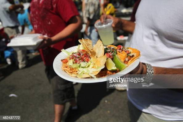 A man carries a plate of tacos at the Hispanic Heritage Festival on July 20 2014 in Valhalla New York Thousands of people gathered for the event to...