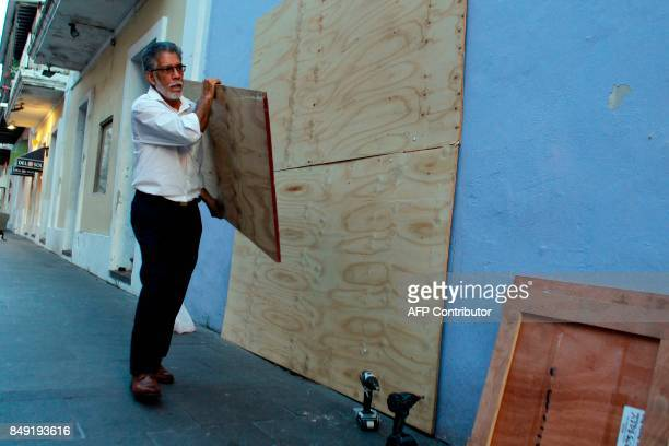 A man carries a plywood board to board up windows of a business in preparation for the anticipated arrival of Hurricane Maria in San Juan Puerto Rico...