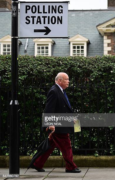 A man carries a polling card as he walks past a polling station sign outside the Royal Hospital in Chelsea west London on June 23 as Britain holds a...