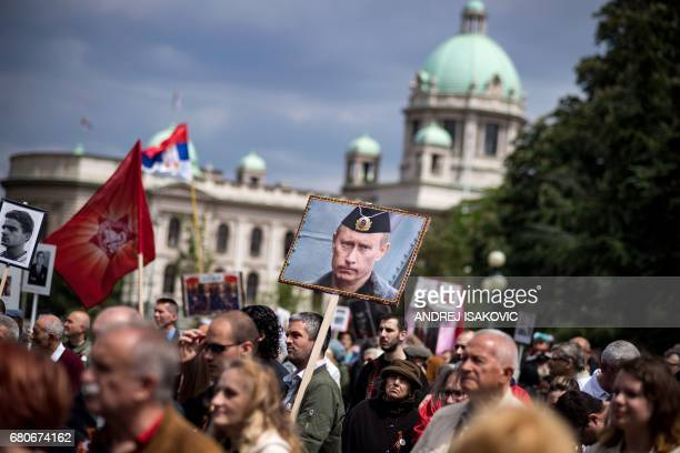 A man carries a portrait of Russian President Vladimir Putin during the Immortal Regiment march in central Belgrade on May 9 2017 Serbia marks the...