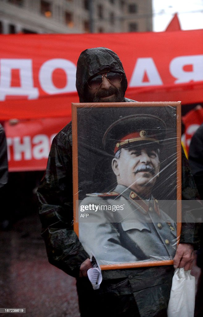 A man carries a portrait of Soviet dictator Josef Stalin as he attends a rally of Russian communist party activists and supporters to mark the 96th anniversary of the 1917 Russia's Bolshevik Revolution in central Moscow on November 7, 2013. AFP PHOTO / VASILY MAXIMOV