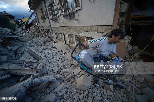 TOPSHOT A man carries a pram among damaged buildings after a strong earthquake hit Amatrice on August 24 2016 Central Italy was struck by a powerful...