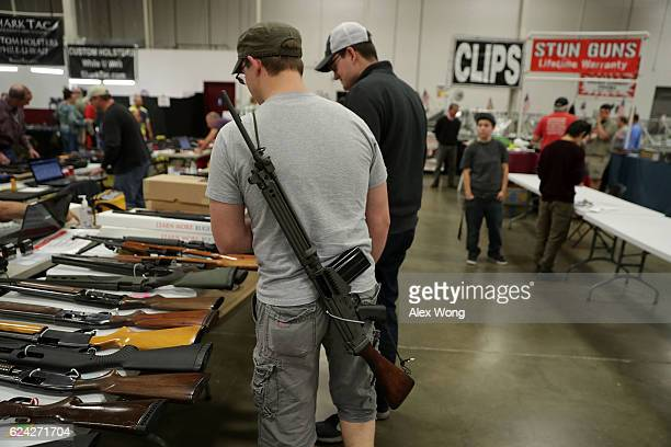 A man carries a rifle on his back during the Nation's Gun Show November 18 2016 at Dulles Expo Center in Chantilly Virginia The show is one of the...