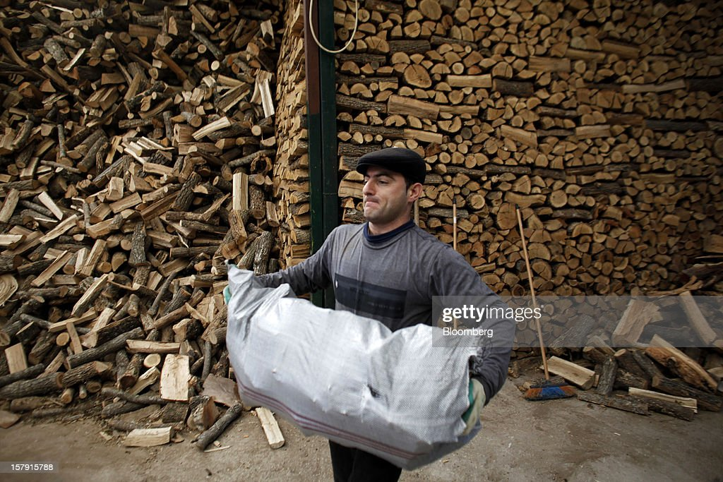 A man carries a sack of logs for a customer in the yard of a wood store in Athens, Greece, on Friday, Dec. 7, 2012. Greece, the epicenter of Europe's debt crisis since revealing a bloated spending gap in late 2009, has faced regular demands to get a firmer grip on the budget or risk being forced out of the euro. Photographer: Kostas Tsironis/Bloomberg via Getty Images