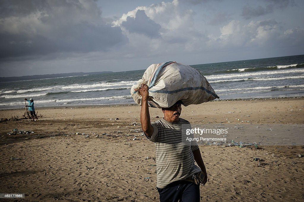 A man carries a sack of plastic waste that he collected at Kuta Beach on January 17, 2014 in Kuta, Indonesia. The sight of trash washed up on Kuta beach has become an annual phenomenon as piles of debris are carried to the beach by strong currents during the winter months. Kuta Beach is one of Bali's top tourist destinations, however during the winter months waste materials are swept up onto the beaches in Java, Bali, and Nusa Tenggara.