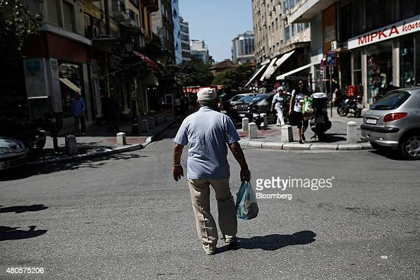 A man carries a shopping bag of goods along a street after visiting Kapani market in Thessaloniki Greece on Monday July 13 2015 Greece has been in...