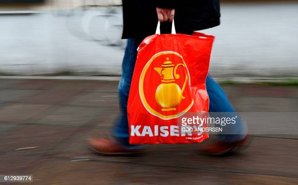 A man carries a shopping bag with the logo of German retail chain Kaiser's of the Kaiser's Tengelmann group in front of a Kaiser's supermarket in...